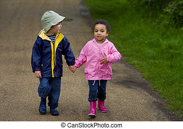 Hand In Hand - A little boy and girl wearing wellington...