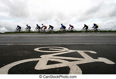 bike race in denmark, cyclist are passing by a bike sign on...