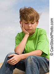 Solemn Thoughts - A downcast child sitting and thinking.