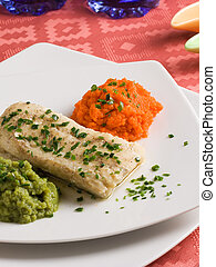 Hake filet with carrots and broccolis purees in an elegant...