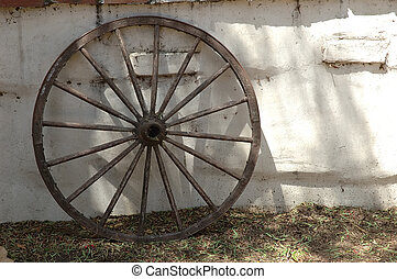 Wagon Wheel against Adobe Wall