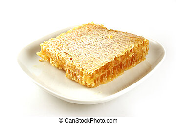 Honeycomb on a plate - Square of honeycomb isolated on a...