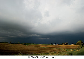 Farm field with background storm - Farm field with impending...