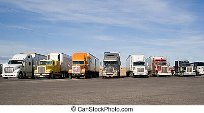 rigs in a row - a group of large trucks in a row