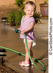 watering - little girl waters using a hose