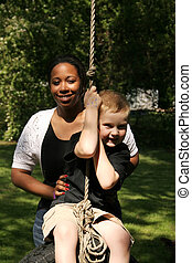 Swinging - A babysitter pushing a child on a tire swing.