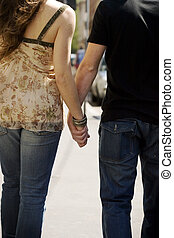 Hands-in-hands - happy couple walking on a street and...