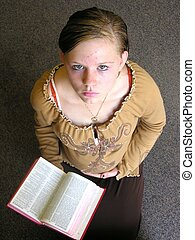 Pregnant girl prays - Pregnant teen holding a bible.