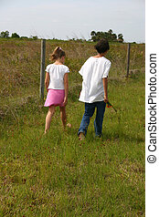 Boy and Girl Walking in a Field - Boy and girl walking in a...