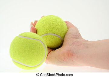 hand with two tennis balls, ball in the foreground is out of...