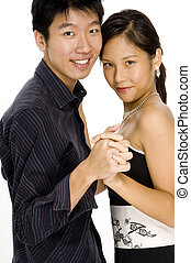 Dancing Couple - A young asian couple stand closely and hold...