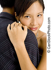 Hug - A young pretty asian woman hugs her man
