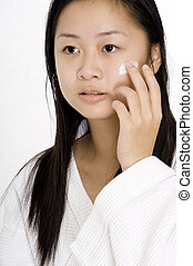 Face Cream - A young chinese woman applying face cream