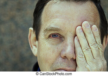 on the one hand - man covering left eye(special photo...