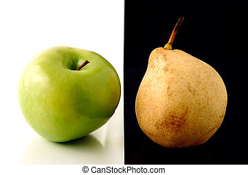 Granny Smith apple and yellow pear on artistic background