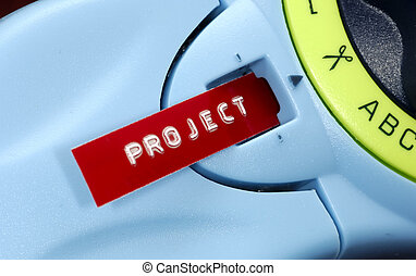 Project Label - Photo of a Label Machine WIth a Label Coming...