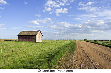 Rural scene - Farmers shed in the fields along side a gravel...