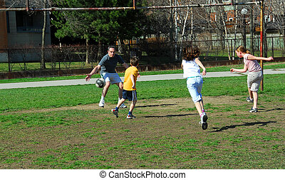 Family soccer game - Family playing soccer in a schoolyard
