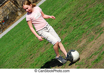 Girl playing soccer - Young girl playing soccer in school...