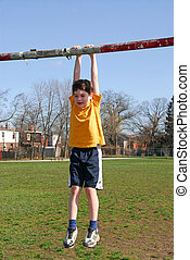 Boy hanging on - Little boy hanging on the soccer gate