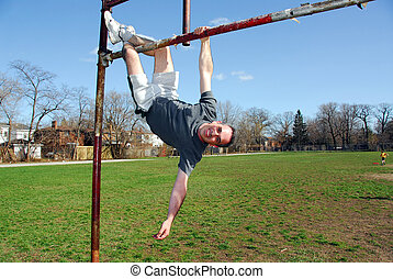 Happy man hanging upside down from a soccer gate