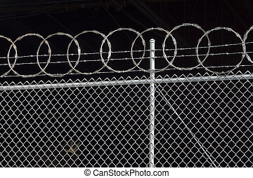 Razor Fence - Razor wire spirals against the dark interior...