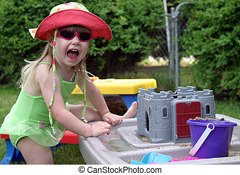 Summer Fun - Young toddler in swimsuit having fun playing...