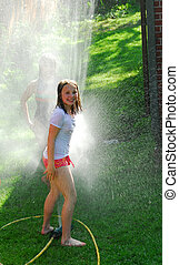 Girls and sprinkler - Girls running though a sprinkler in a...