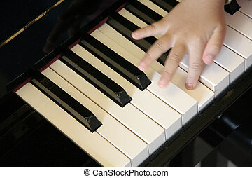 child hands on a piano keyboard