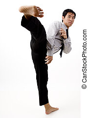 Karate Kick - A young businessman throws a high kick towards...