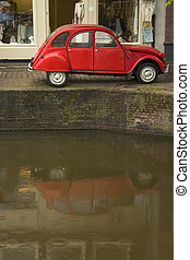 Old red car parked along a canal