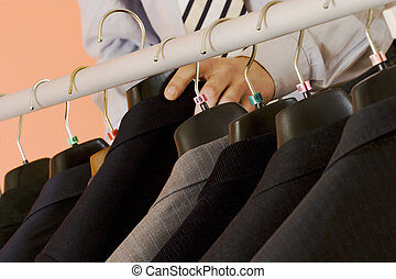 choosing the suit - the man is chosing the right suit for...