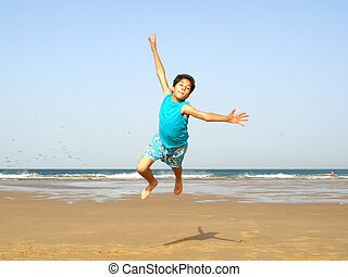 Boy jumping - boy flying on the beach