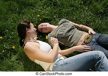 freetime - two girls enjoying their freetime laying in the...
