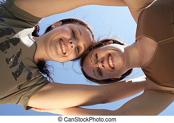 friendship - two girls holding each other while smiling in...
