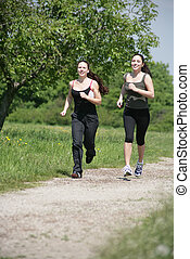 activity - two girls are jogging in the nature