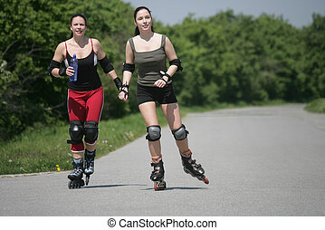 blading - two girls are skating  in the nature
