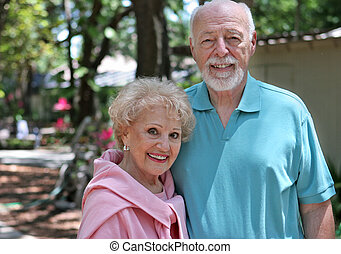 Senior Couple In Garden - An active senior couple walking...