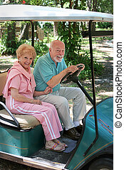 Golf Cart - Seniors - An active senior couple driving a golf...
