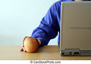 Apple and laptop - Businessman working on a laptop and...