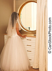 Wedding 42 - Bride standing in front of a mirror in a room