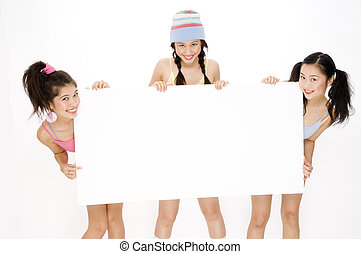 Girls and Sign - Three pretty teens holding a large blank...