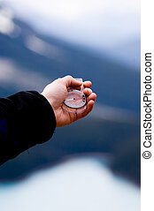 Finding direction - Hand with compass in the mountains