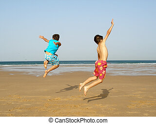 Boys jumping - Two boys jumping of joy on the beach