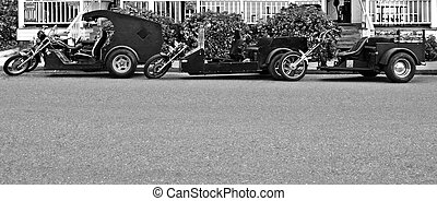 Three Black and White Trikes parked along curb