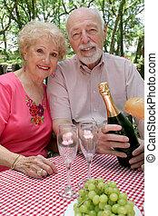 Seniors Picnic - An attractive senior couple enjoying a...