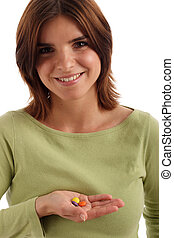 Taking a pill - Portrait of a young pretty woman holding a...