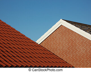 Red tile roof with blue sky as background