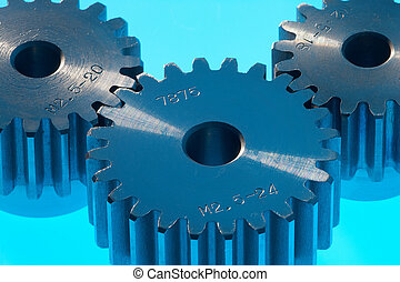 metal cannon - cantle of three metal cogwheels on blue...