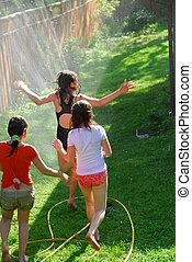 Girls run sprinkler - Young girls running through sprinkler...